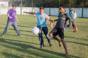 Student volunteers James Dubuisson (left), Nick Smirniotopoulos (center) and some of their teammates (right, background) enjoy a friendly soccer match with Brazilian children during a World Cup outreach project in Rio de Janeiro. IMB/Lina White.